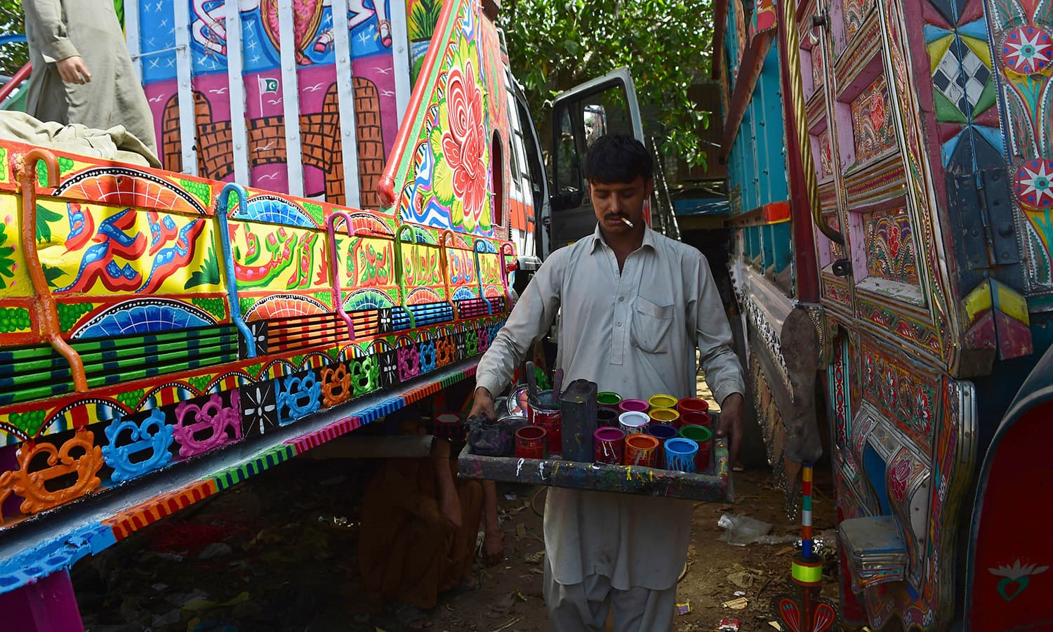In this photograph taken on May 4, 2015, a painter prepares to finish decorating a truck at his workshop in Rawalpindi.