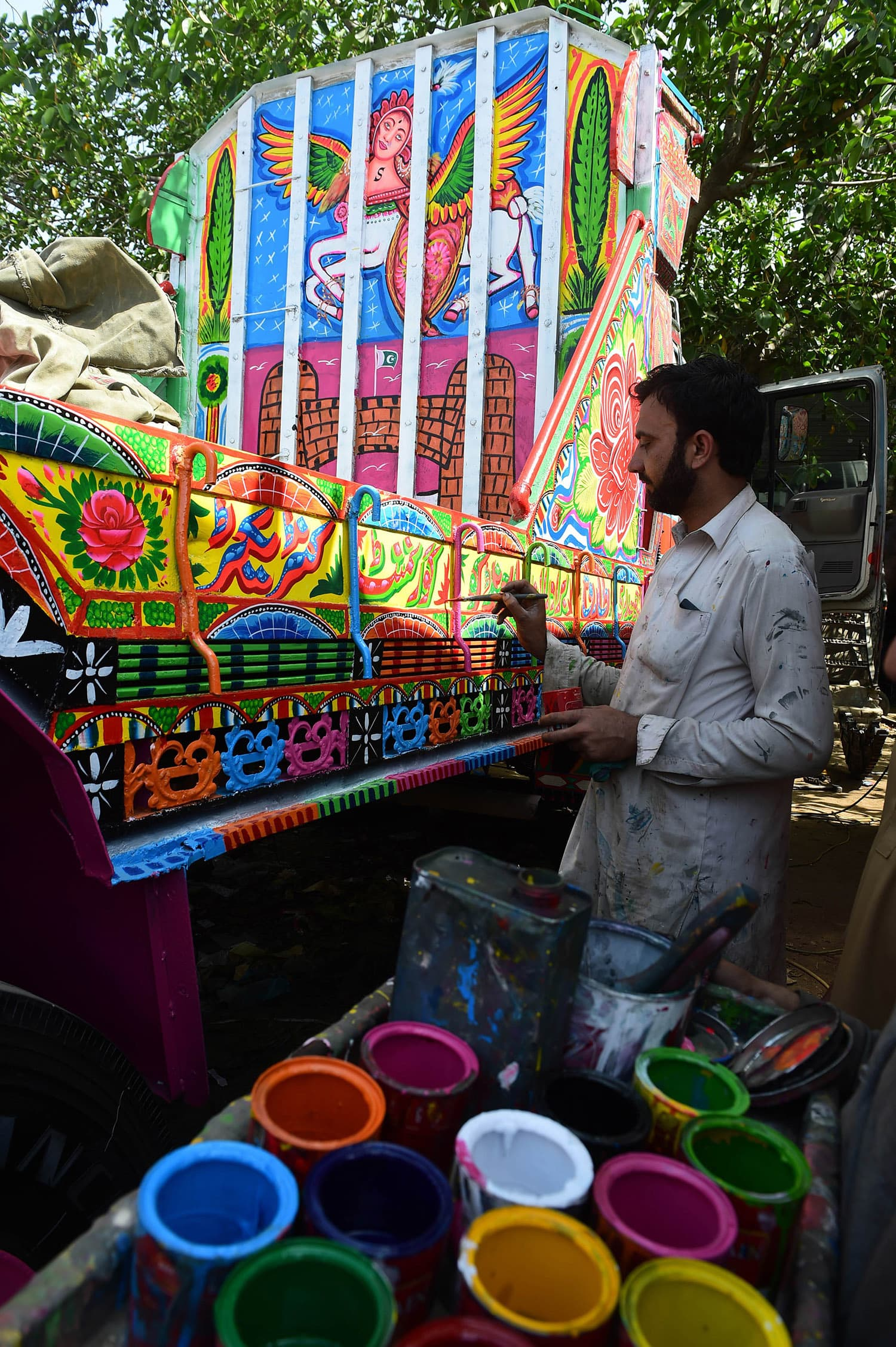 Painter Rashid decorates a truck at his workshop in Rawalpindi.