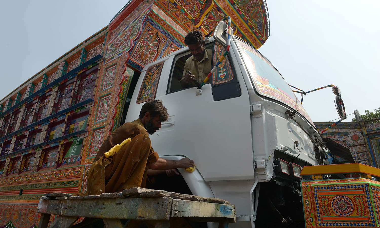 Painters decorate a truck in Rawalpindi.