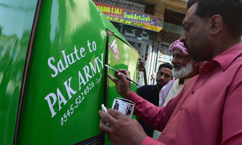 Painter Ijaz (far R) decorates a rickshaw outside his workshop in Rawalpindi.