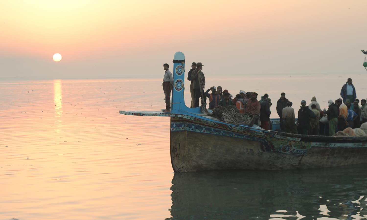 Fishermen return from a trip while the sun is pictured setting in the background.