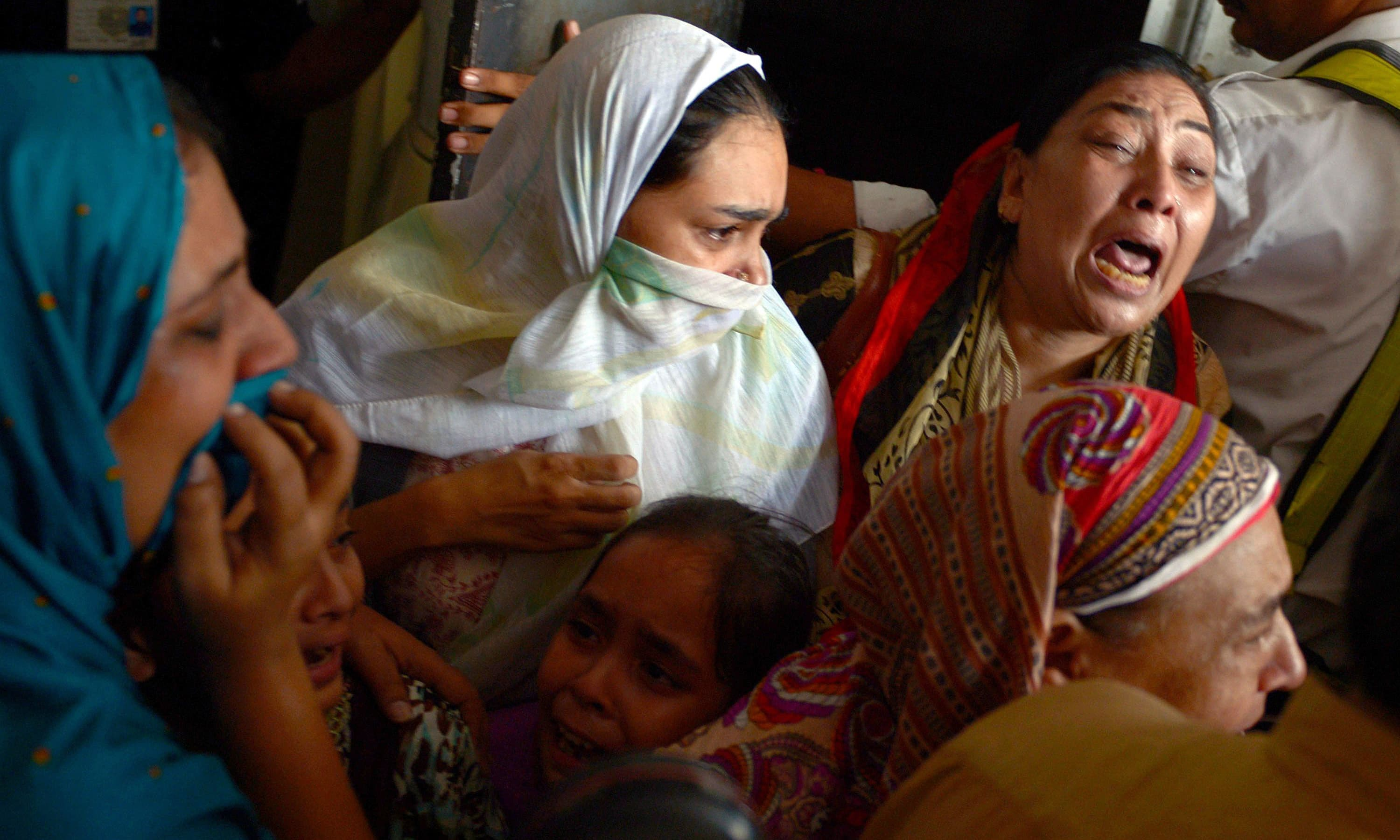 Relatives mourn after body of Saulat Mirza arrives in Karachi. ─ AFP