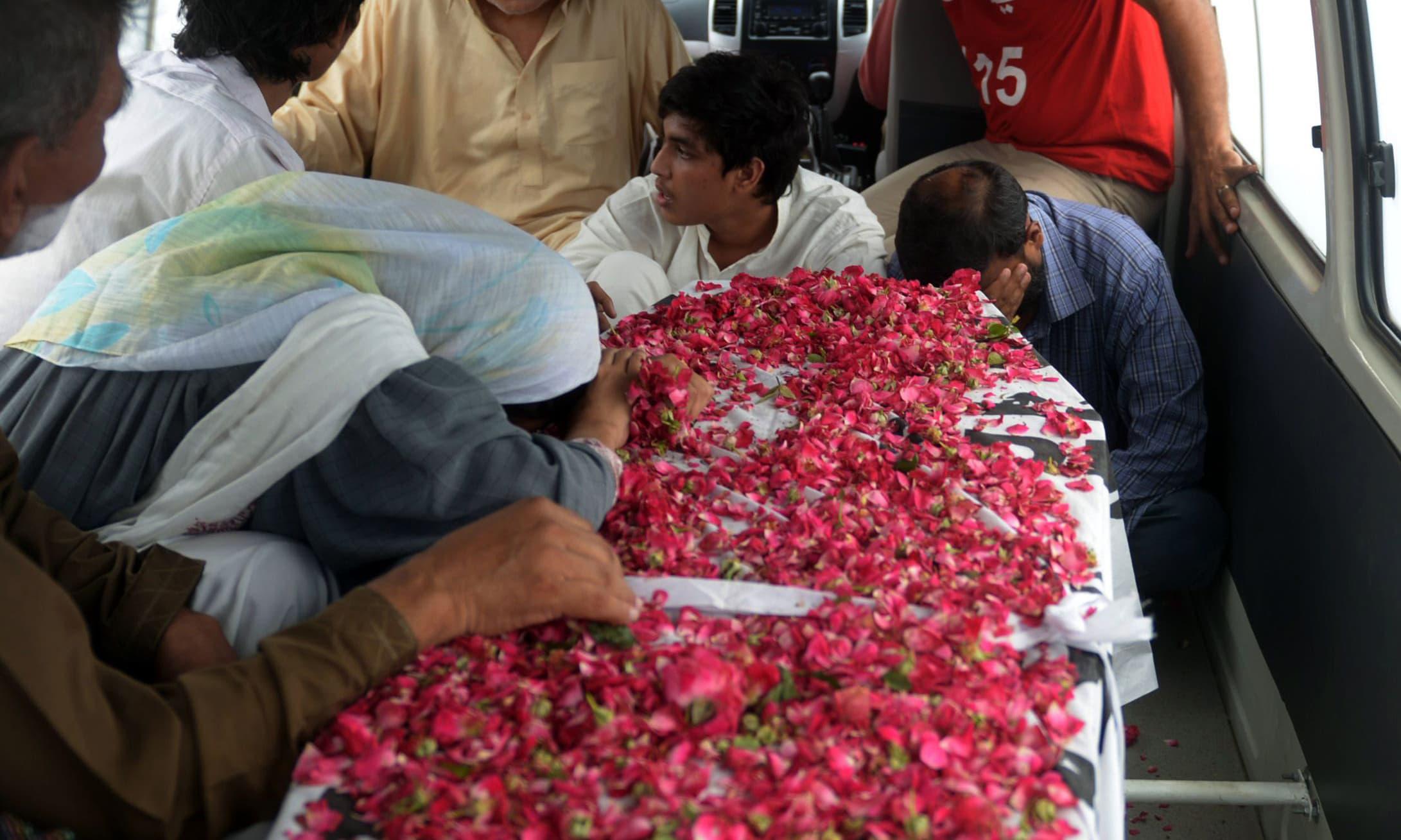Relatives react next to Saulat Mirza's coffin. ─ AFP