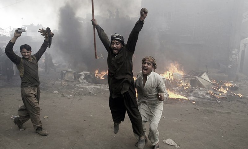 Men, part of an angry mob, react after burning belongings of Christian families, Lahore, March 9, 2013. —AP/FILE