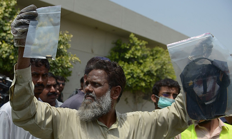 A plain-clothes police official holds up evidence collected from the scene of an attack by gunmen on a bus carrying Ismailis in Karachi on May 13, 2015.— AFP