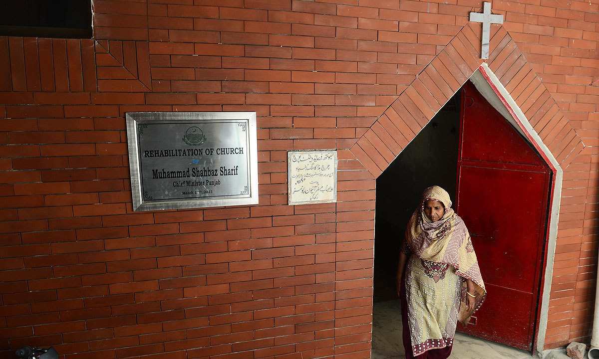 A woman walks out of a church after it was restored by Punjab Chief Minister Shahbaz Sharif | Arif Ali, White Star