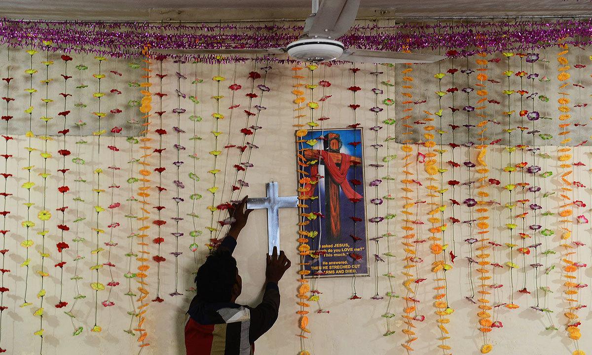 A man hangs a cross inside a church   White Star