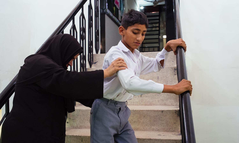 ایک ٹیچر ایک بچے کو سیڑھیاں اترنے میں مدد دے رہی ہیں۔