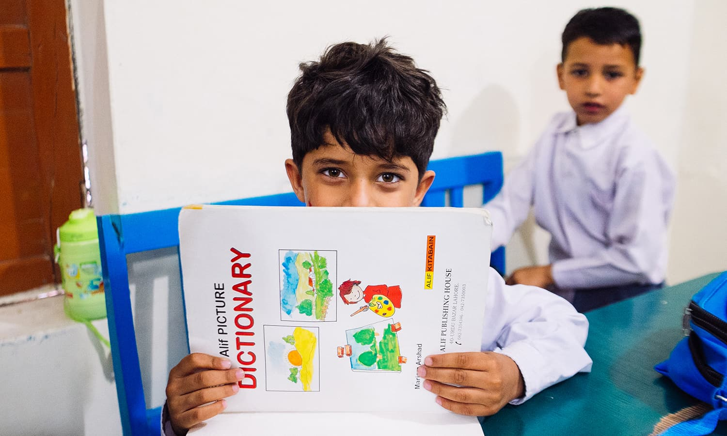 A boy peers over a textbook.