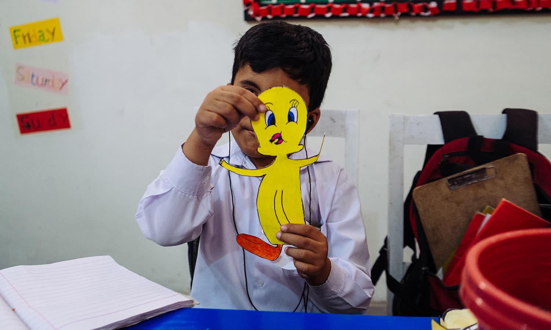 ایک بچہ اپنا کلاس ورک دکھاتے ہوئے۔
