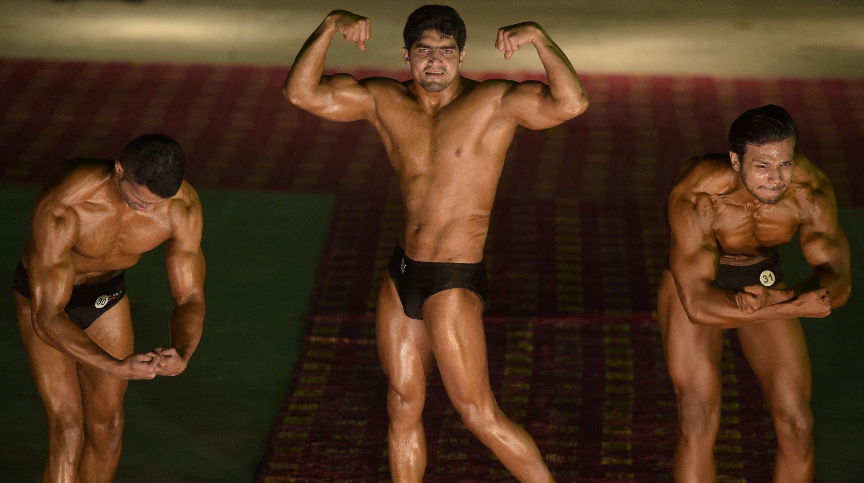 Bodybuilders pose during the competition. — AFP
