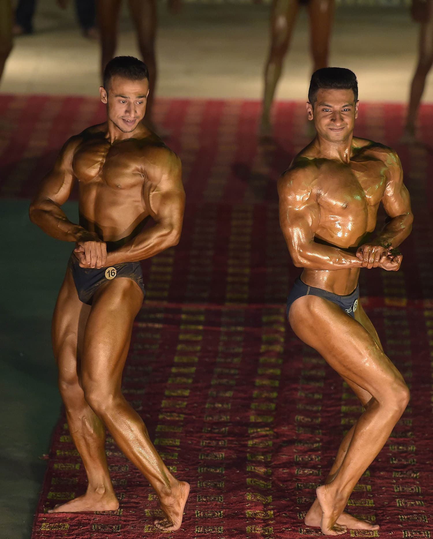 Bodybuilders flex during compete during a local Mr Islamabad and junior Mr Islamabad competition. — AFP