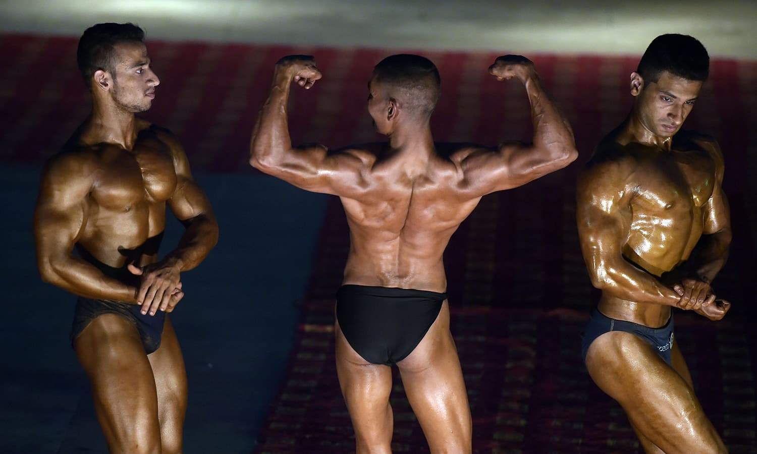Bodybuilders compete during a local Mr Islamabad and junior Mr Islamabad competition in Islamabad. — AFP