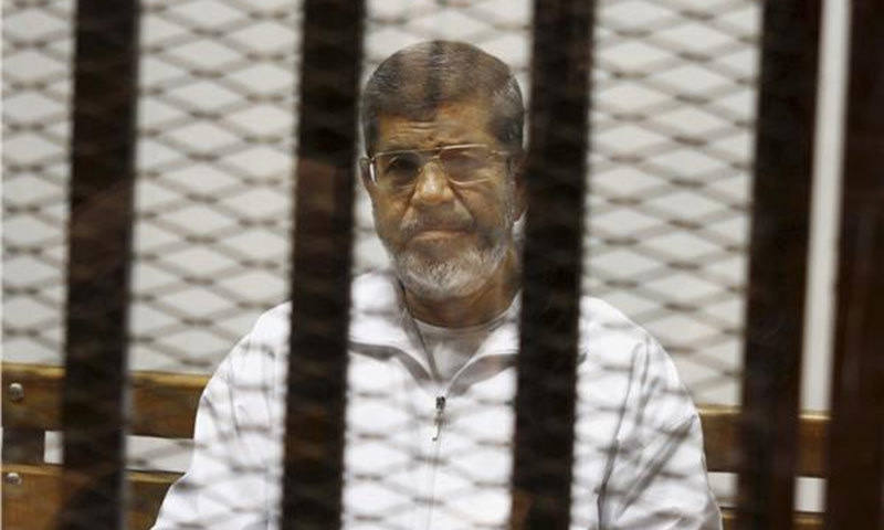 Egypt's ousted Islamist President Mohammed Morsi sits in a defendant cage in the Police Academy courthouse in Cairo.— AP