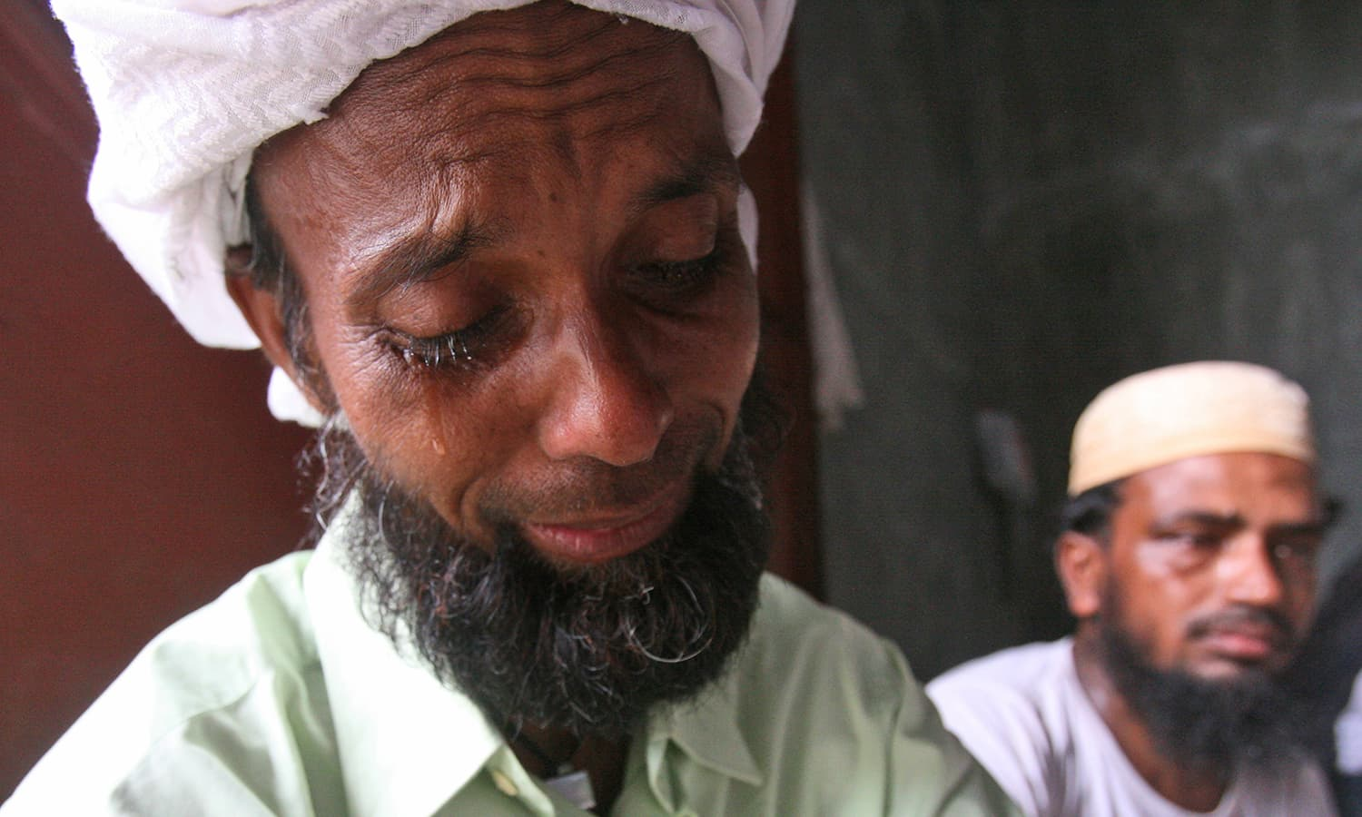 A Bangladeshi migrant weeps during the visit of Bangladesh's Ambassador to Indonesia Mohammad Nazmul Quaunine at a temporary shelter in Langsa, Aceh province, Indonesia.
