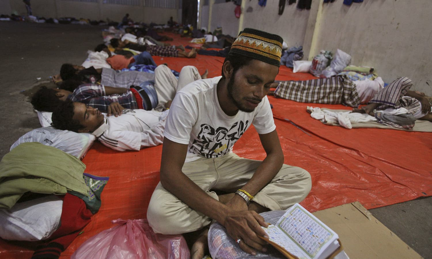 A migrant reads the Muslim holy book of Quran at a temporary shelter in Langsa, Aceh province, Indonesia.