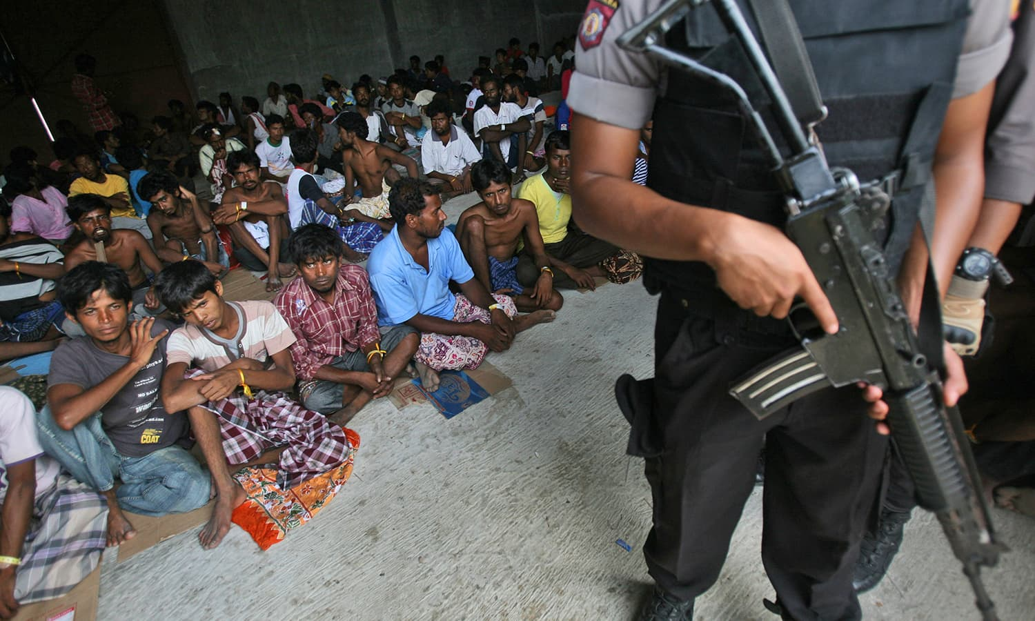 An armed Indonesian police officer stands guard during the visit of Bangladesh's Ambassador to Indonesia Mohammad Nazmul Quaunine at a temporary shelter in Langsa, Aceh province, Indonesia.