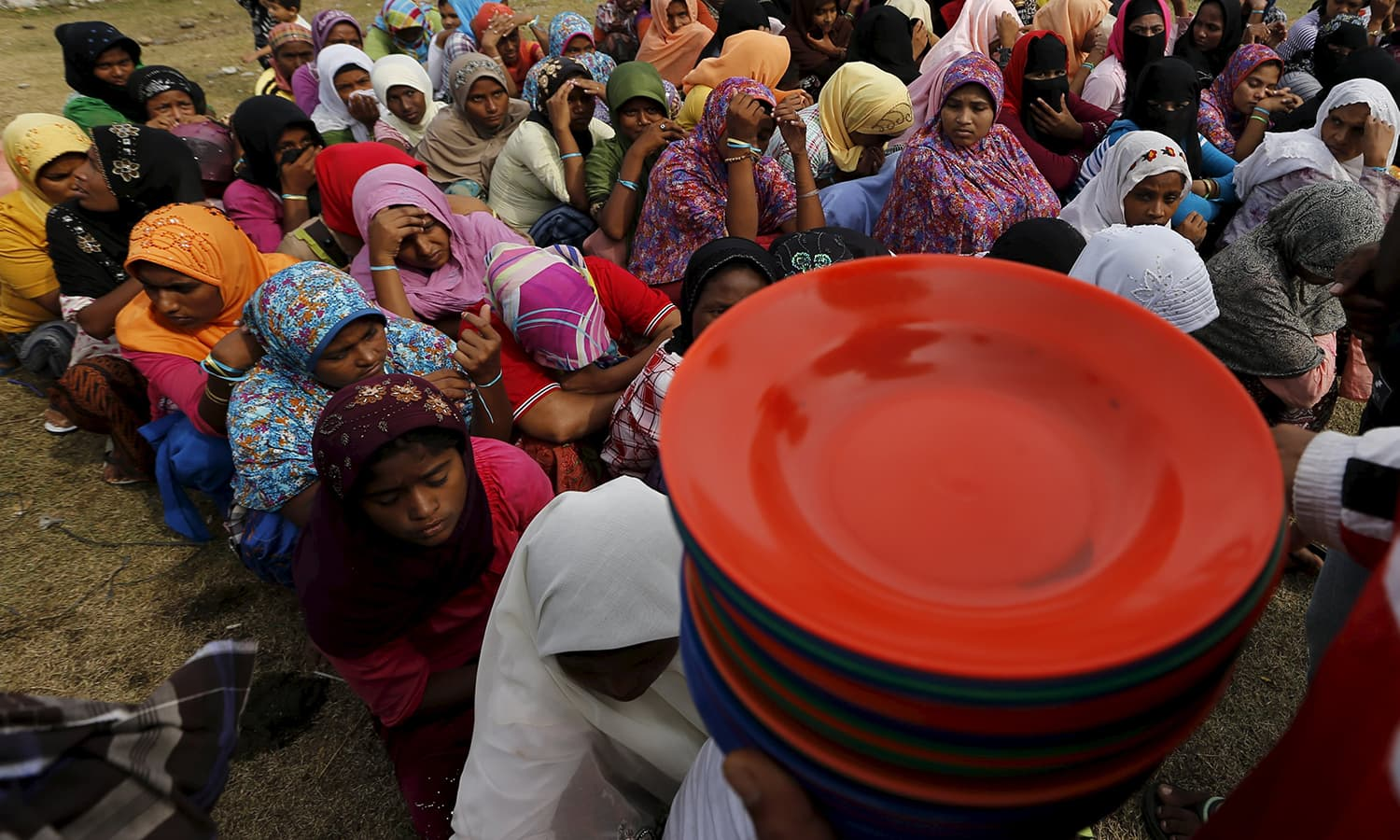 An Indonesian Red Cross volunteer holds plates for Rohingya migrants who arrived in Indonesia by boat during breakfast inside a temporary compound for refugee at Kuala Cangkoi village in Lhoksuko.