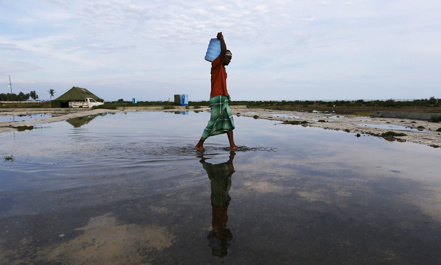 A Rohingya migrant, who arrived in Indonesia by boat, carries a gallon of drinking water inside a temporary compound for refugees in Kuala Cangkoi village in Lhoksukon, Indonesia's Aceh Province May 17, 2015. Nearly 800.