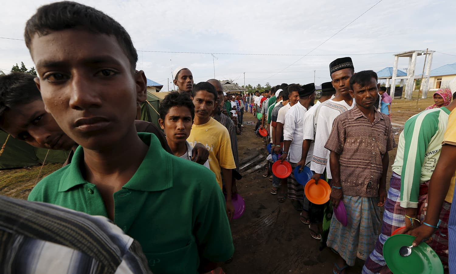 Rohingya migrants who arrived in Indonesia by boat queue for breakfast inside a temporary compound for refugee at Kuala Cangkoi village in Lhoksukon.