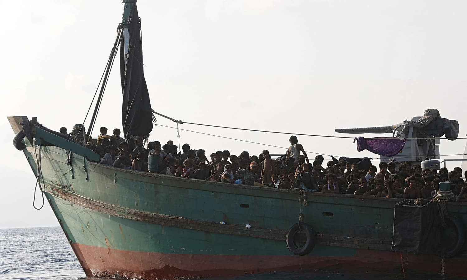 "A boat crammed with migrants was towed out to sea by the Thai navy and then held up by Malaysian vessels on Saturday, the latest round of ""maritime ping-pong"" by Asian states determined not to let asylum seekers come ashore."