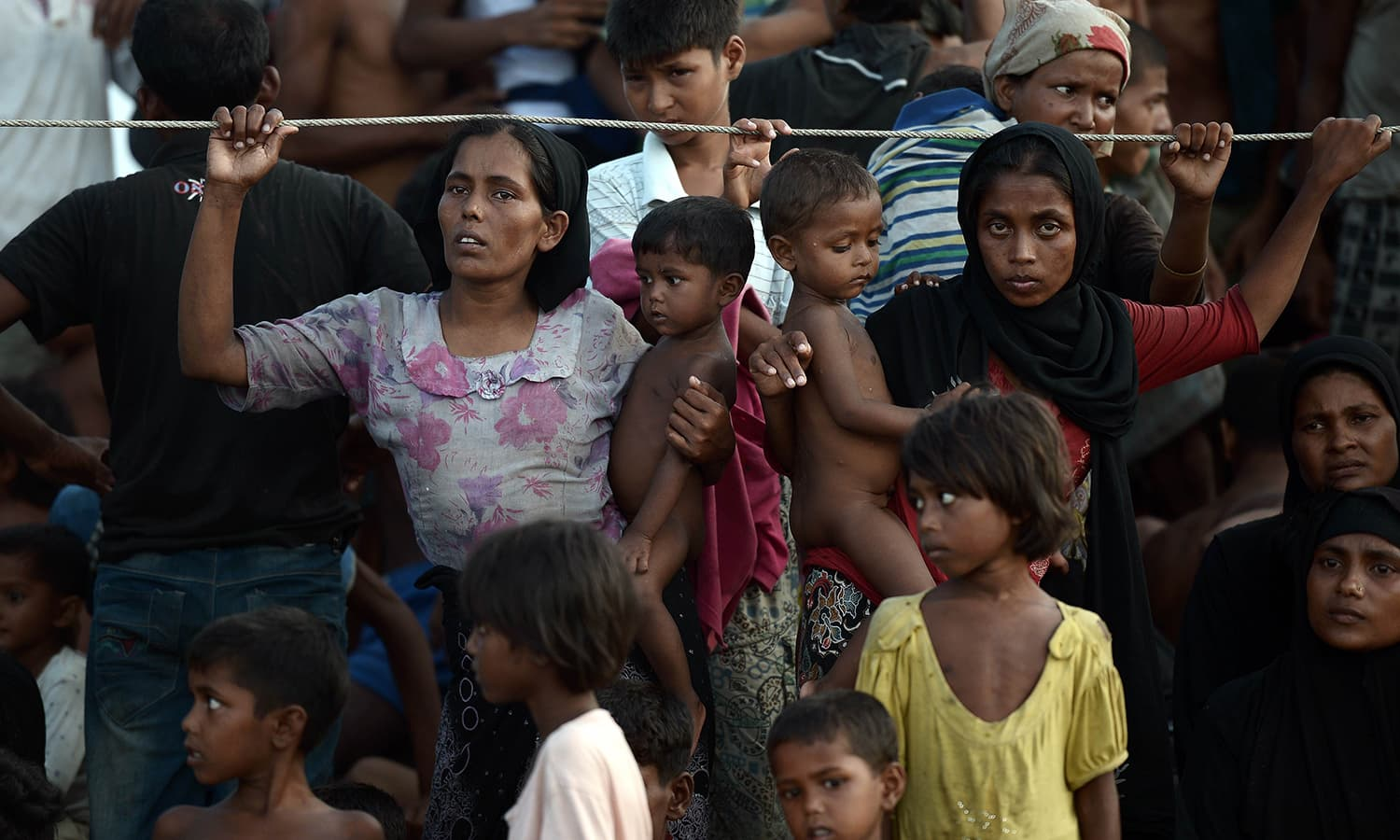 Rohingya migrant women holding children as they stand on a boat drifting in Thai waters off the southern island of Koh Lipe in the Andaman. AFP