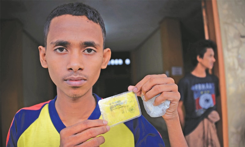 MUHAMMAD Shorif displaying his UNHCR identification card while temporarily housed at a government sports auditorium in Lhoksukon, located in Indonesia's Aceh province. He came ashore to Aceh with other Muslim Rohingya after a harrowing, month-long boat journey.—AFP
