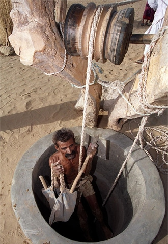 In search of water, a Thari villager climbs down into a dried up well to dig deeper - AFP file photo