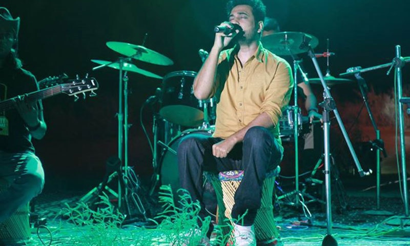 Saif Samejo sits on a traditional 'moorha' as he sings for the audience. — Photo courtesy: The Sketches' Facebook Page