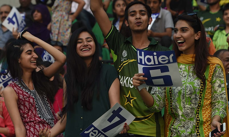 Spectators cheer their team as they attend the first T20 match between Pakistan and Zimbabwe in Lahore. — AFP