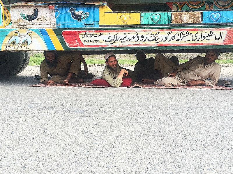 Drivers rest under their monstrous trucks in the late evening, before they set out towards Torkham. These guys were happy to pose.