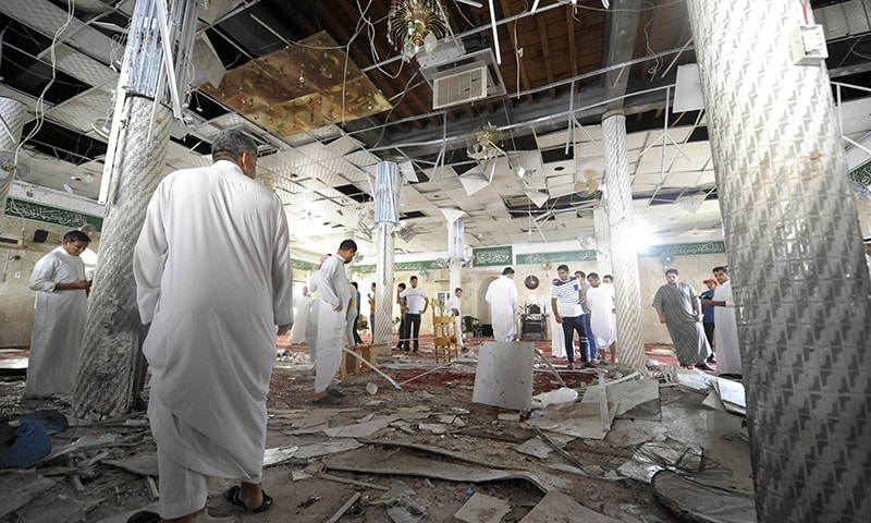 Saudi men gather around debris following a blast inside a mosque, in the mainly Shia Saudi Gulf coastal town of Qatif, 400 kms east of Riyadh, on May 22, 2015. — AFP
