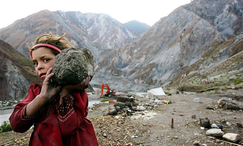 A Kashmiri refugee carries a stone to help her father build a wall in the Neelum Valley near the earthquake-devastated city of Muzaffarabad back in 2006. — Reuters/ File