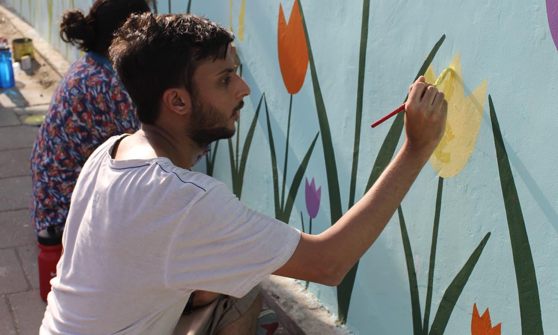 انڈس ویلی اسکول کے طلبہ ایم ٹی خان روڈ کی دیوار پینٹ کر رہے ہیں