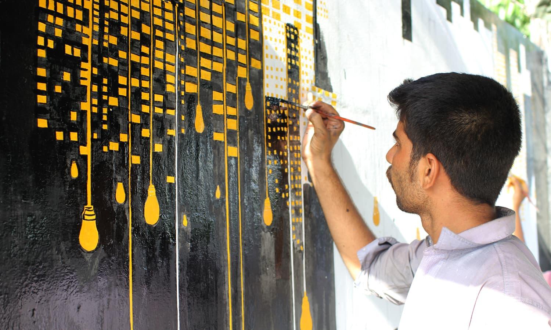 ایک طالب علم ایم ٹی خان روڈ پر دیوار پینٹ کر رہا ہے