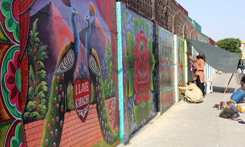 کراچی کے مشہور ٹرک فنکار ایم ٹی خان روڈ پر دیوار پینٹ کر رہے ہیں