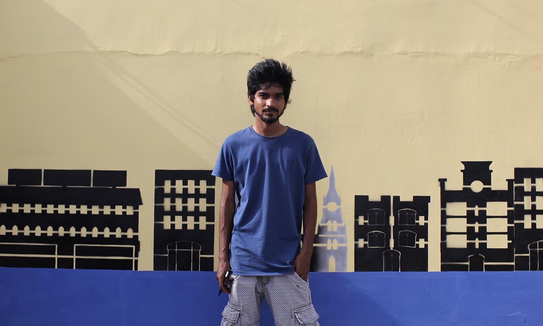شیخ محمد ذاکر اپنی پینٹ کی ہوئی دیوار کے سامنے کھڑے ہیں