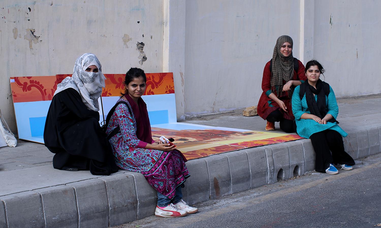 پینٹ کرنے کے بعد طلبہ دیوار کے سامنے بیٹھے ہوئے ہیں
