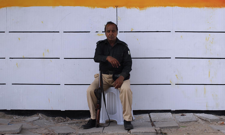 Police man guarding the newly painted wall at MT Khan Road, Karachi