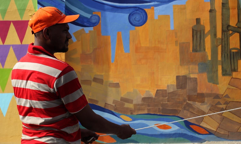 فنکار دیوار پر پینٹ کر رہا ہے