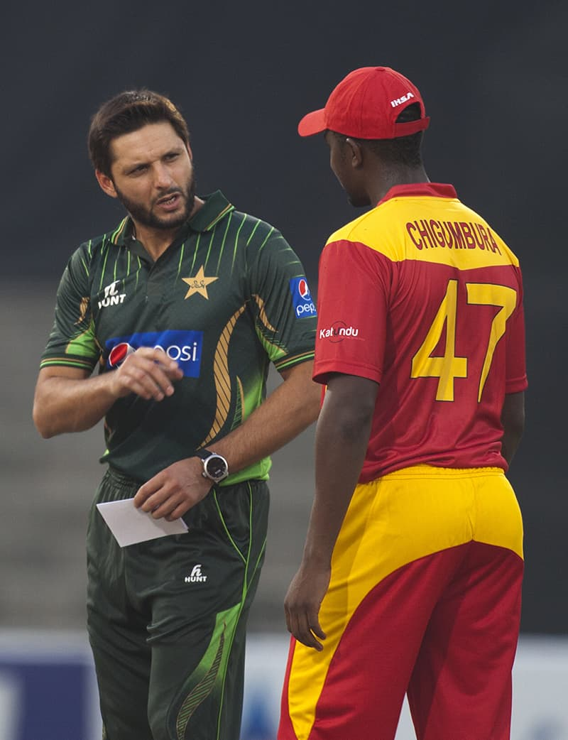 Shahid Afridi, left, offers batting to Elton Chigumbura captain of guest team Zimbabwe after winning toss at the Gaddafi Stadium in Lahore. — AP