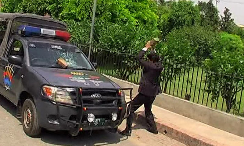 A lawyer is seen throwing bricks at a police van during protests. —DawnNews screengrab