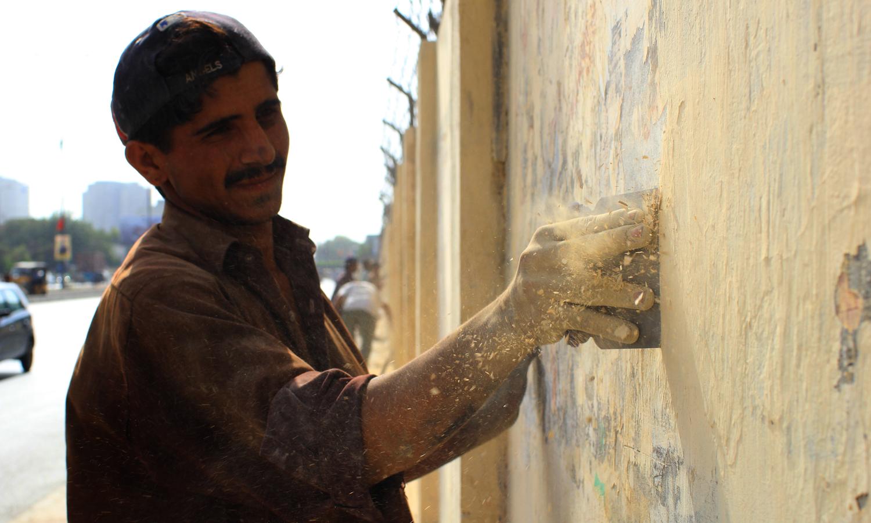 ایم ٹی خان روڈ پر مزدور دیوار سے پینٹ ہٹا رہا ہے۔