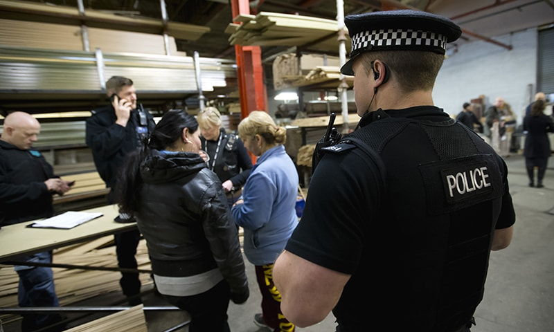 In this Dec 15, 2014 photo, a police officer looks on as interviews are conducted with factory workers after Greater Manchester Police officers alongside partner agency teams from Rochdale Council, the Home Office and Her Majesty's Revenue and Customs, raided a picture framing factory in Rochdale, Northern England, investigating trafficking for sham marriages. —AP