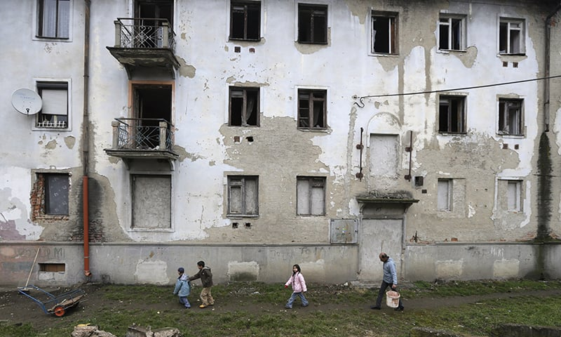 In this March 2, 2015 photo, residents walk past their house in a Roma settlement in Kralovsky Chlmec, Slovakia. —AP