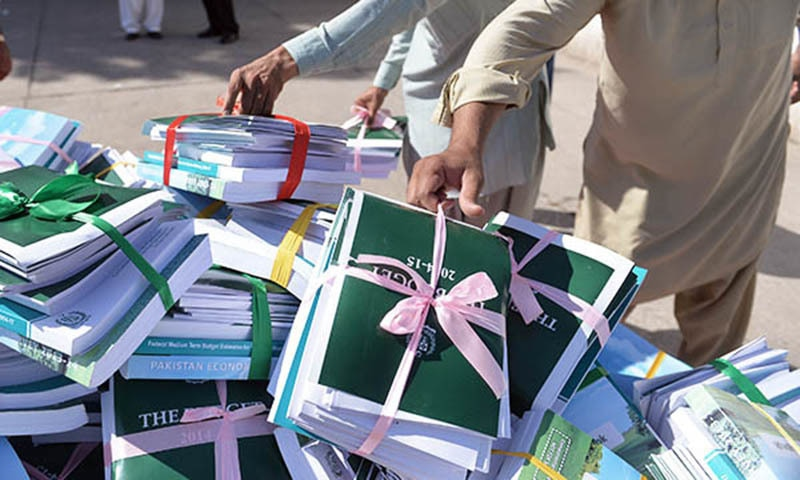 A Pakistani National Assembly employee carries copies of the state budget to be distributed to parliamentarians at the Parliament House building in Islamabad on June 3, 2014 | AFP