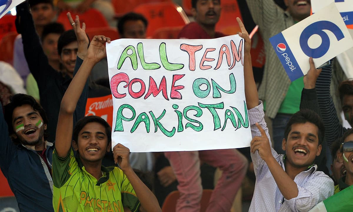 Spectators carry a placard before during the first ODI between Pakistan and Zimbabwe at the Gaddafi Stadium in Lahore. — AFP