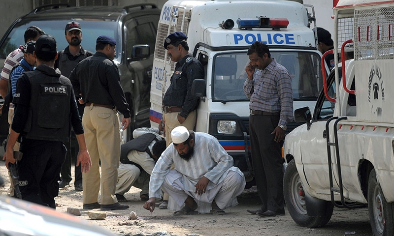 Security personnel collect evidence after an attack on a police vehicle in Karachi on May 27, 2015. — AFP