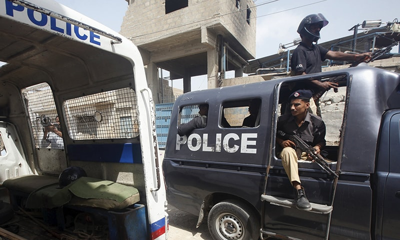 A police van passes a damaged police vehicle with blood stains, after three policemen were killed by unidentified gunmen, in Karachi, Pakistan, May 27, 2015. — Reuters