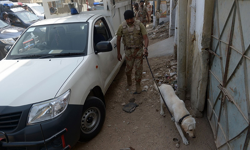 A Ranger  collects evidence with the help of a dog after an attack on a police vehicle in Karachi on May 27, 2015.  — AFP